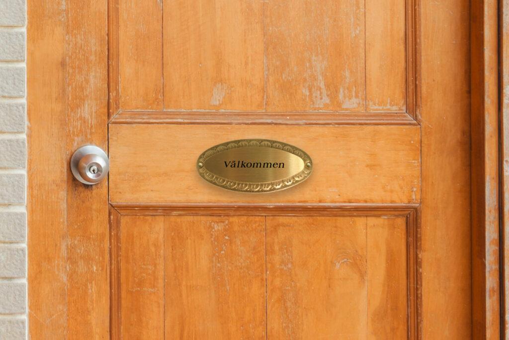Graverad namnskylt på dörr i mässing